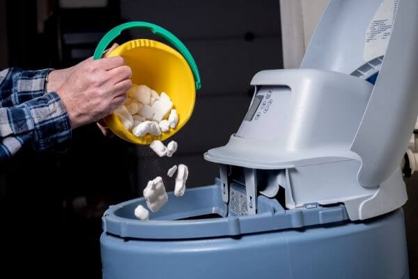 A man pours salt into a Kenmore water softener